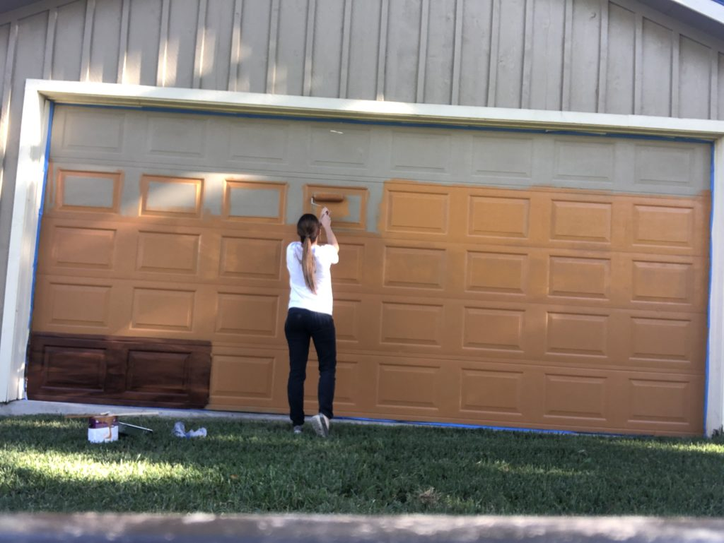 Shelby rolling on the orange base coat on the garage door for the faux wood painting project